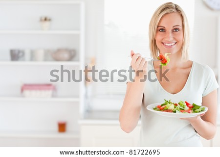 Close up of a cute woman eating salad in the kitchen