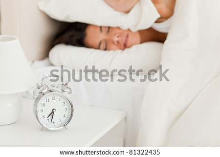 close up of a cute woman waking under sheet not wanting to hear alarm clock in bedroom