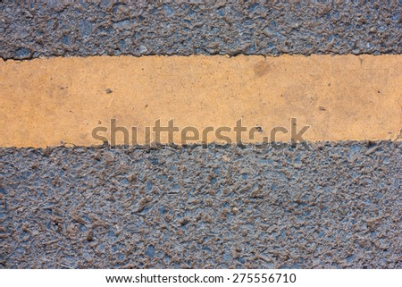 close up of a dark grey asphalt road divided by yellow paint - stock photo