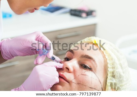 Close-up of a dark-haired woman an Asian beautician injecting a syringe for injection of Botox into the cheekbones of a young woman to adjust the shape in the medical office