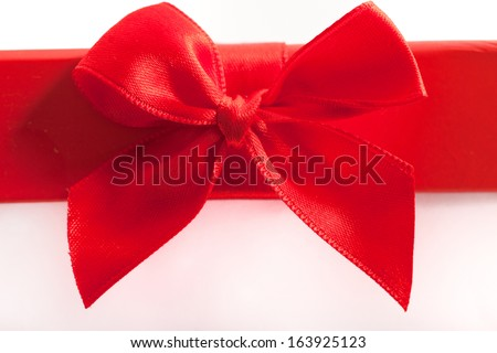 Close up of a decorative romantic red bow on a Christmas or Valentines gift over a white background with copyspace for your message or seasonal greeting