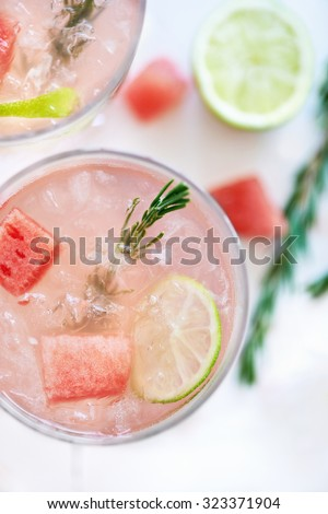 Close up of a delicious pink girly feminine cocktail mocktail drink with slices of watermelon, lime and rosemary