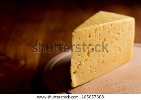 Close up of a delicious wedge of fresh cheese on a wooden cheese board with copy space - stock photo