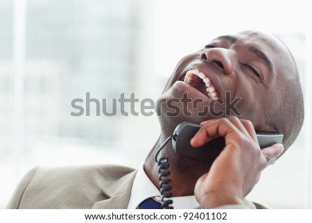 Close up of a delighted businessman on the phone in his office - stock photo