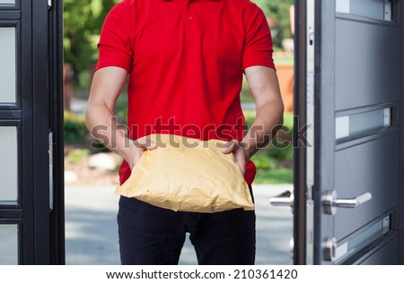 Close-up of a delivery man giving a package - stock photo