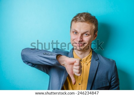 Close-up of a disappointed young business man showing thumb down sign