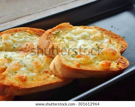 Close-up of a dish of garlic bread with cheese. - stock photo