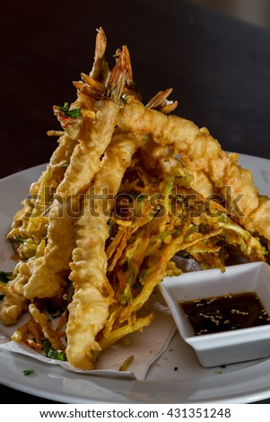 close up of a dish with tempura fried shrimp and vegetables with a soy sauce dipping sauce - stock photo