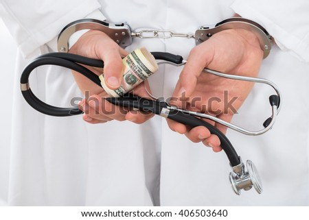 Close-up Of A Doctor Hands Holding Bank Notes And Handcuffs
