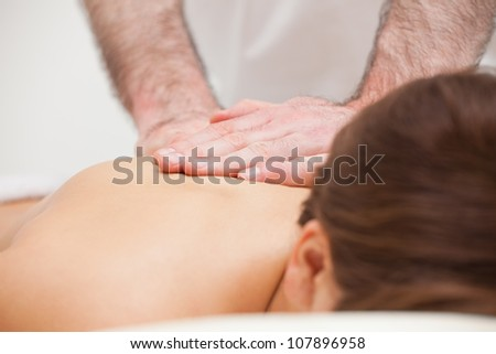 Close-up of a doctor massaging the back of a woman indoors - stock photo