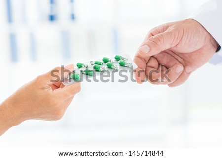 Close-up of a doctor's hand giving a blister card with capsules to the patient - stock photo