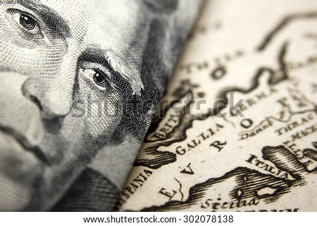 Close-up of a 20-dollar banknote (figuring president Jackson) and an old map of Europe  - stock photo