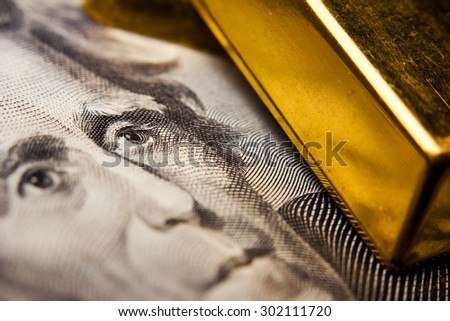 Close-up of a 20-dollar banknote (figuring president Jackson) and gold ingots - stock photo
