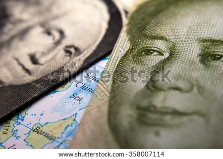 Close-up of a 1 dollar note (figuring George Washington) and Mao Zedong on a 1 yuan Chinese banknote on top of a map showing the South China Sea - stock photo
