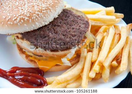 Close-up of a double hamburger and french fries, studio shot - stock photo