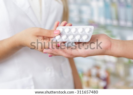 Close up of a druggist giving pills to the customer  - stock photo