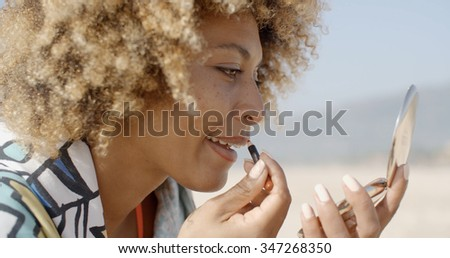 Close-up of a ed beautiful woman doing makeup
