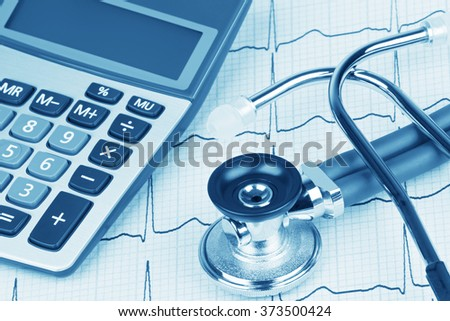 Close up of a Electrocardiograph also known as a EKG or ECG graph with a stethoscope and calculator showing the high cost of health care