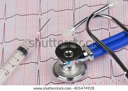 Close up of a Electrocardiograph also known as a EKG or ECG graph with a stethoscope and syringe - stock photo