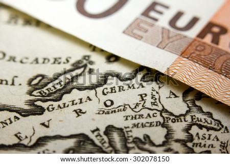 Close-up of a 50-euro banknote and an old map of Europe - stock photo