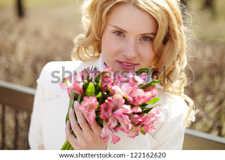 Close-up of a face of a beautiful girl holding flowers