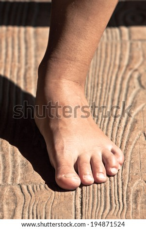 Close up of a female barefoot leg on wooden floor.