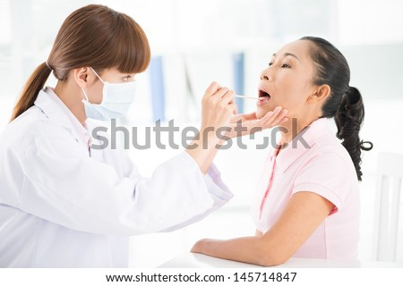 Close-up of a female doctor examining a patient's throat