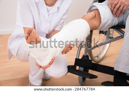 Close-up Of A Female Doctor Holding Disabled Patient's Leg - stock photo