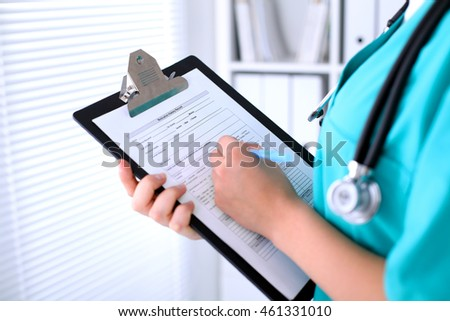 Close-up of a female doctor is filling  out application form or medical history