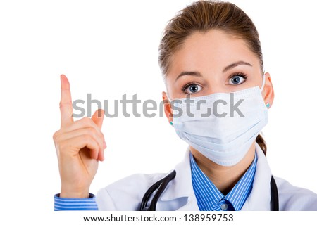 Close-up of a female doctor wearing a mask and pointing with her finger on a copy-space