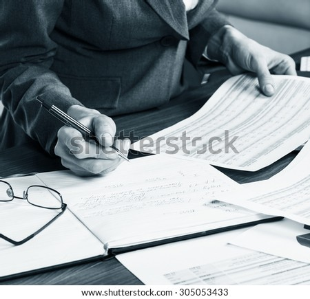 Close up of a female hand calculating, on the office desk.