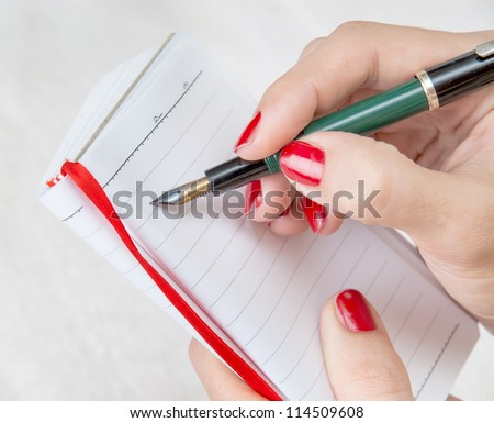 Close Up Of A Female Hand Holding A Pen About To Take Notes On A Blank Note Pad - stock photo