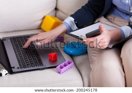 Close-up of a female hands typing on laptop and colorful kids toys - stock photo