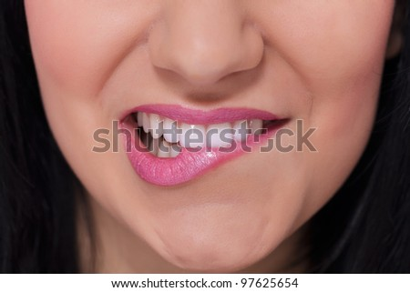 Close-up of a female lips biting  white teeth - stock photo
