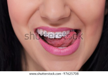 Close-up of a female mouth and white teeth which she touches with her tongue - stock photo