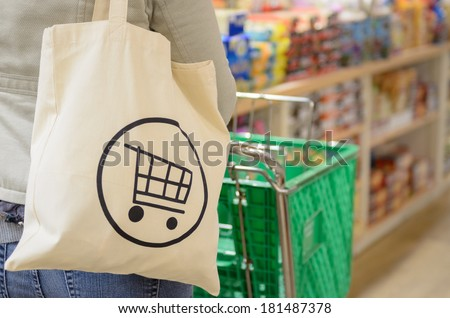 Close up of a female shopper with a canvas tote bag pushing a shopping cart down the isle of a specialty grocery store. - stock photo