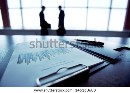 Close-up of a financial report with the silhouettes of business people in the background
