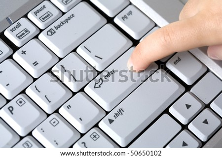 Close up of a finger pressing the enter key on a keyboard.