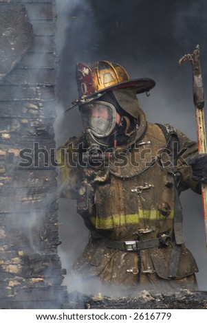 Close-up of a Fireman in a window fighting the blaze - stock photo