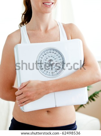 Close-up of a fit hispanic woman holding a scale in her living-room at home