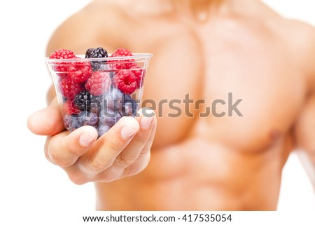 Close-up of a fit man holding a bowl of fresh red fruits, isolated on white background - stock photo