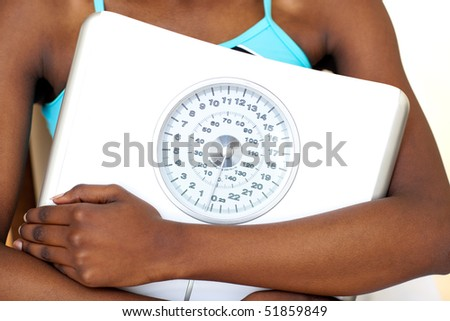 Close-up of a fitness woman with thumb up holding a weight scale against a white background