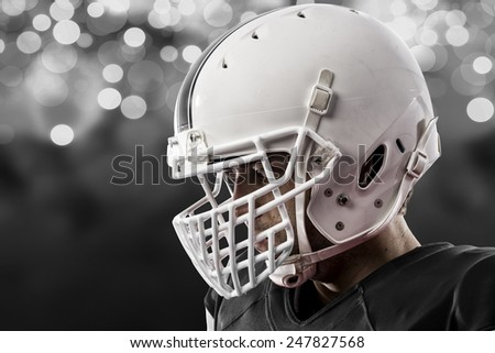 Close up of a Football Player with a black uniform on a black lights background. - stock photo