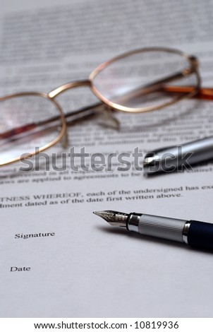 close-up of a fountain pen and eyeglasses over a business contract to be signed