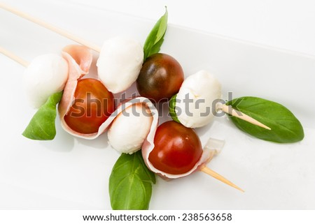 close up of a fresh mozzarella and tomato appetizer with basil and proscuitto on a white plate - stock photo