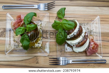 close up of a fresh mozzarella and tomato salad served in slices and stacked with a side of proscuitto - stock photo