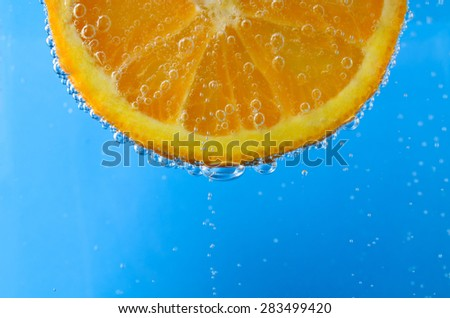 Close up of a fresh orange slice at top of image and facing forwards, suspended in sparkling bright blue water.  Oxygen bubbles float upwards and cover the front and edges of the fruit. - stock photo