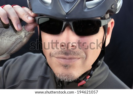 Close-up of a friendly bicycle courier putting on his sunglasses.