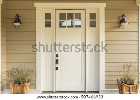 Close up of a front door with small square decorative windows and flower pots