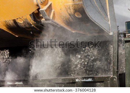 Close-up of a front-end loader unloading ore into truck - stock photo